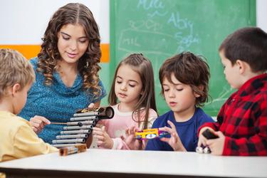 professeur de musique explique le xylophone à des enfants de maternelle
