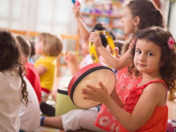 Enfant de 4 ans jouant du tambourin dans un groupe de musique